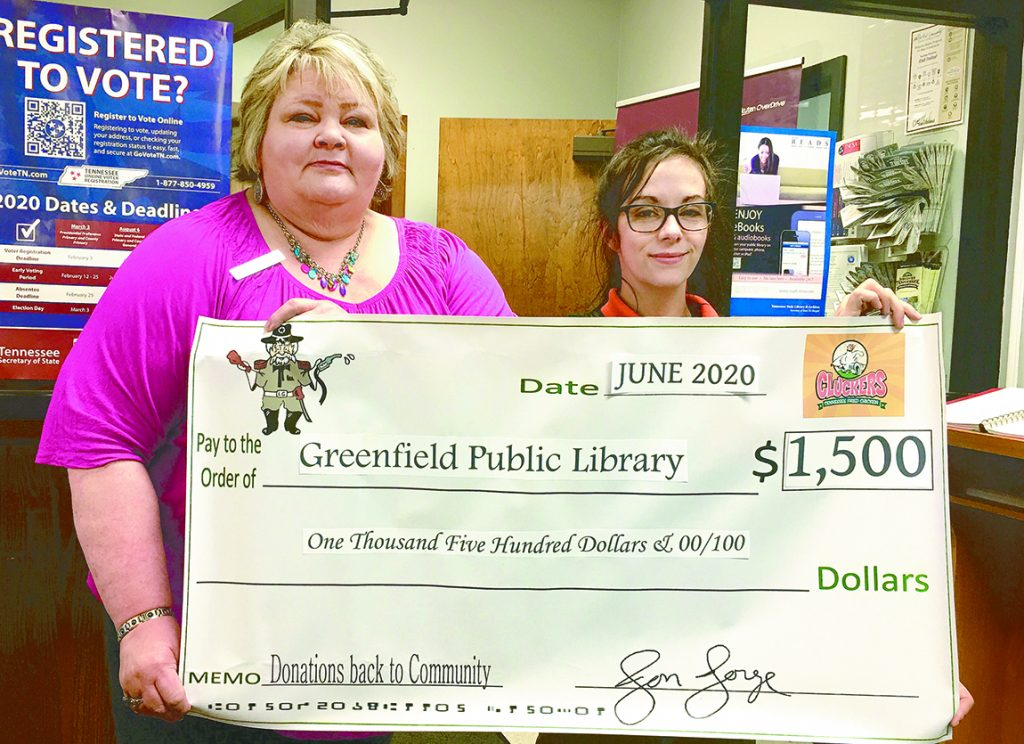 Cox Oil Company representative Kelsey Thomas, Mgr. of Greenfield Little General, presents a $1,500 check to Kathy Watson, Library Director.