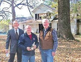 Joe Atnip (left), who is first cousin twice removed to Herschel Jennings Priestley (H.J.), a prior owner and resident of the home; Tony Winstead (center), current owner of the historic home; and Keith Priestley (right), great nephew to H.J. Priestley, stand in front of a 170-year-old house in Dresden. Winstead displays an old grape juice bottle found hidden inside the floor of the historic residence. The bottle contains a message from Priestley containing information about the history of the home.