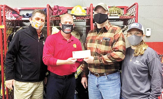 CHECK PRESENTED TO LOCAL NON-PROFIT — Josh Wilson, Martin Fire Department (2nd from L), presented a $250 check to Mike and Jennifer Wenz of the Anna Kate Wenz FIGHT Foundation on December 30, 2020. Martin Kiwanis club president-elect John Mayros (left) was present for the brief ceremony held at the fire station. Wilson earned the $250 after being named the Louisiana-Mississippi-West Tennessee Kiwanis District Fireman of the Year.